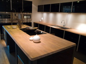 Black high-gloss kitchen with wooden countertops - Photo: © Depositphotos / ronyzmbow