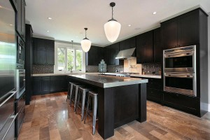 Large kitchen with a cluster-free, simple design. The kitchen island not only works as a central feature but doubles up to provide extra storage and can be used as a large dining table or bar - © Depositphotos / lmphot