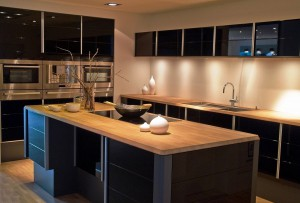 Beautiful contrast: Kitchen with black cabinetry and massive wood © Depositphotos / ronyzmbow