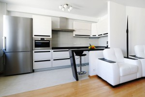 Mainly white open plan kitchen with sophisticated black details.