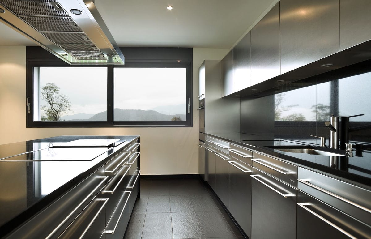 Stainless steel kitchen with black countertops and backsplashes