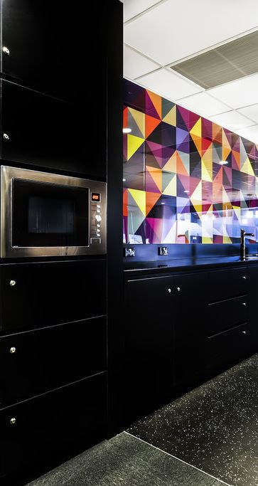Black kitchen with colorful wall tiles.